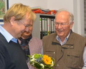 Blümchen für gesammelte Ortsgeschichte: Bürgermeister Christian Thiede bedankt sich bei Wolfgang Heun (r.) für seine Arbeit am Archiv von Rambin.