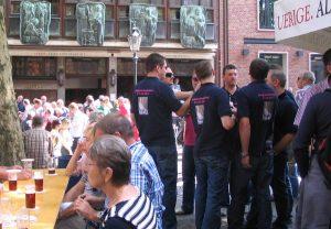 """Kult in Nordrhein-Westfalen: """"Der Uerige"""", die urige Altstadtkneipe in Düsseldorf ist eine Legende. An warmen Sommertagen ist die ganze Straße belebt. Das """"Alt"""" wird dann oft zum Fenster herausgereicht. Foto Wikimedia Commons, Kürschner."""